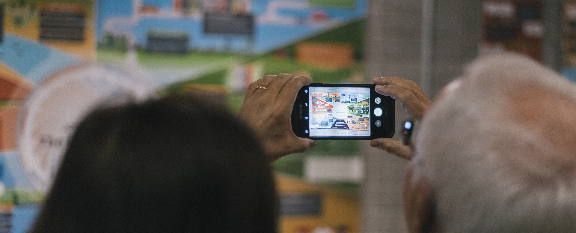 visitor takes photograph of Living City Art Exhibition using phone